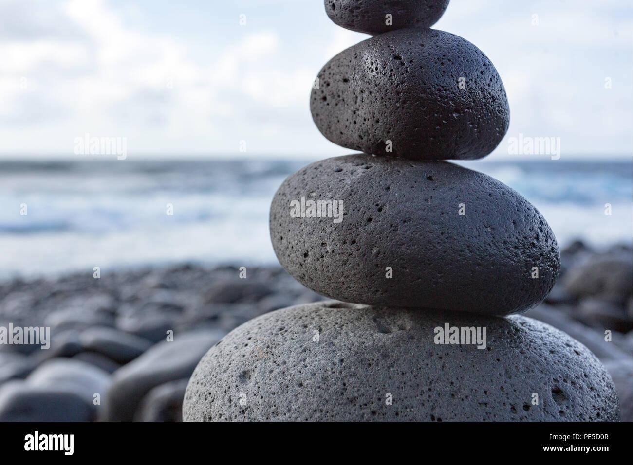 Detail einer ausgewogenen gestapelte Steine oder Kieselsteine am Strand mit dem Horizont im Hintergrund. Stockfoto