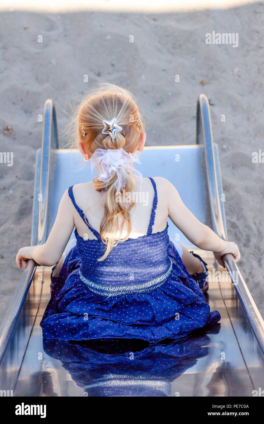 Süße kleine Mädchen Spaß haben auf Folie auf einem Spielplatz im Freien im Sommer. Stockbild