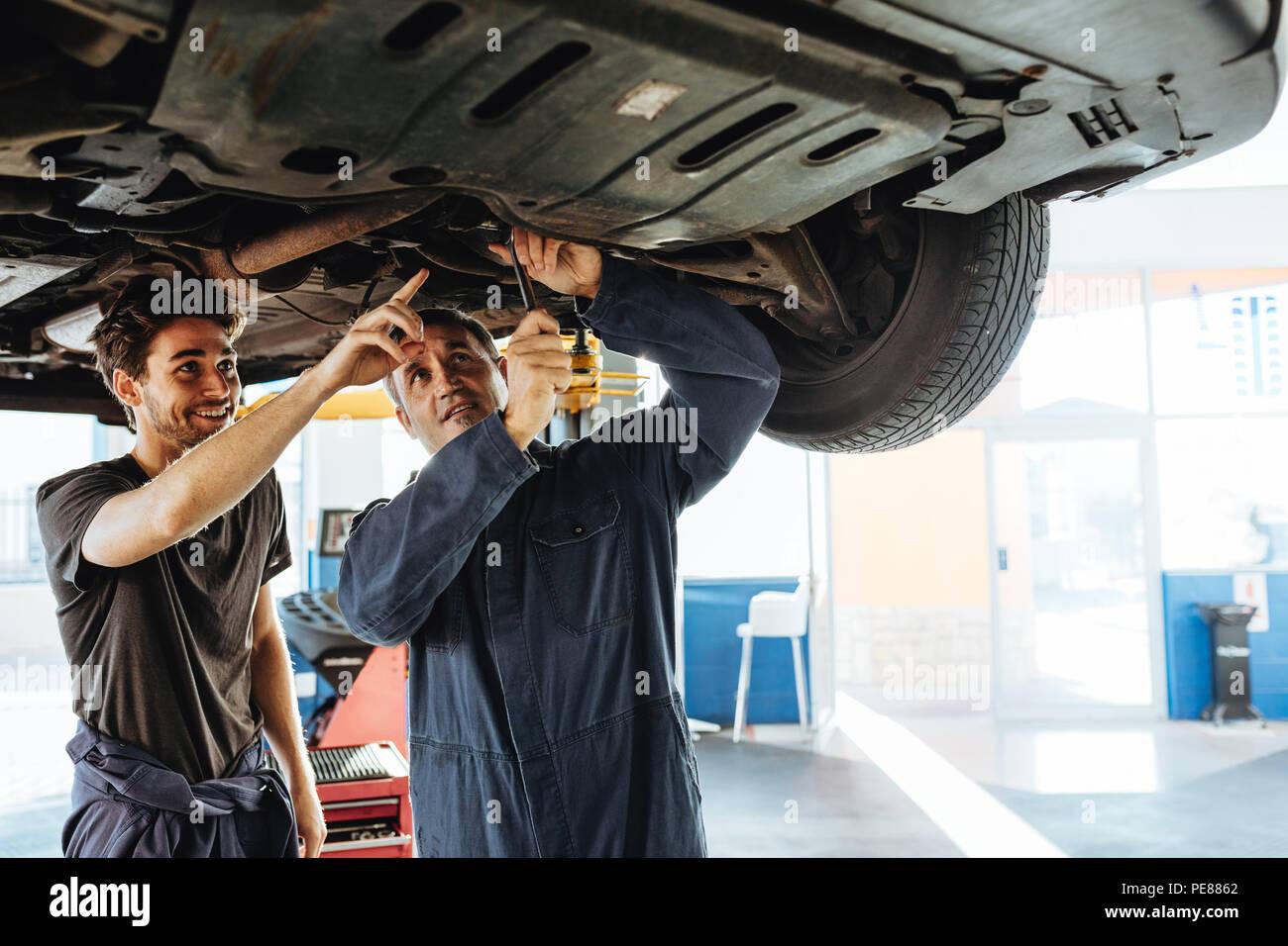 Mechaniker zur Festsetzung der Auto mit Kollegen zeigen und lächelnd. Zwei Auto Reparatur Männer unter einer angehobenen Fahrzeug in der Garage arbeiten. Stockbild