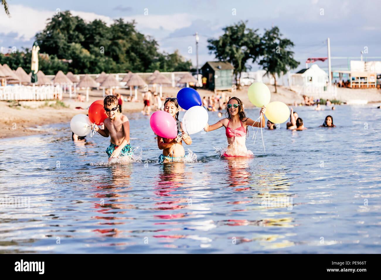 Glückliche Kinder spielen mit Ballons im Meer. Kinder Spaß im Freien. Sommer Urlaub und gesunden Lebensstil Konzept Stockbild