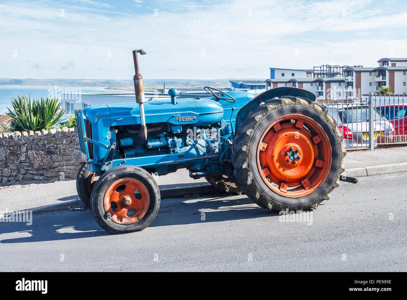 """Alte blaue Fordson Major Traktor mit roten Räder in """"Westward Ho!, Devon, Großbritannien Stockfoto"""