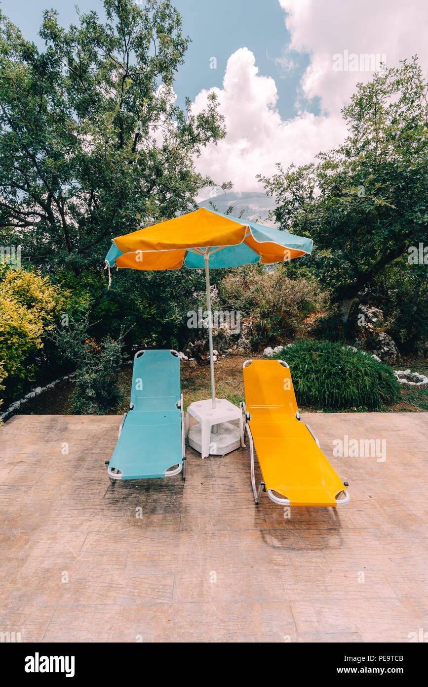 Zwei Liegestühle und ein Sonnenschirm am Pool mit Berge und Wolken im Hintergrund. Perfekter Urlaub Konzept. Foto in Gre genommen Stockbild