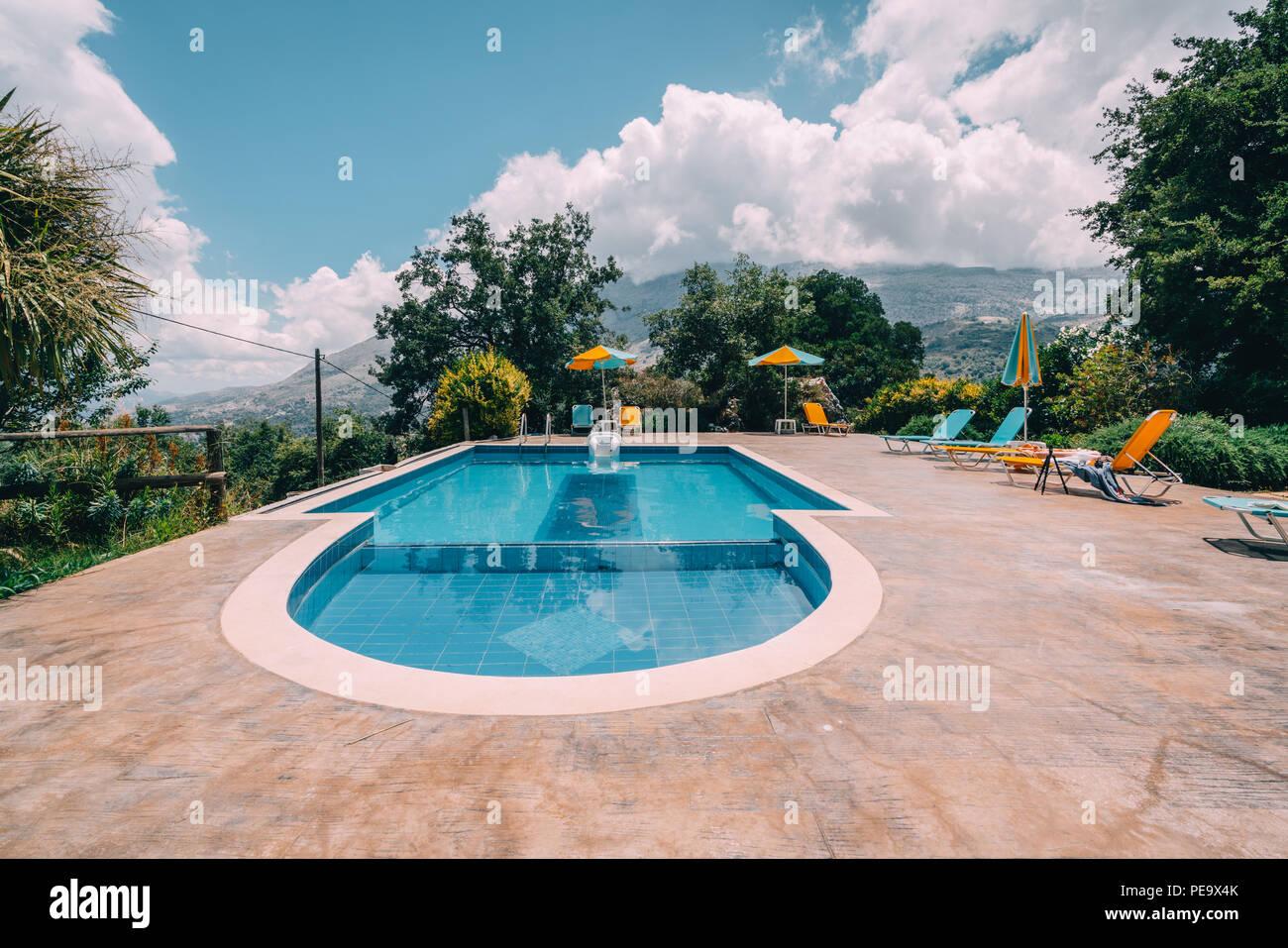Wunderschöne Aussicht auf Pool und clourful liegen in Richtung Berge und blauer Himmel mit Wolken. Foto auf Kreta, Griechenland. Stockbild