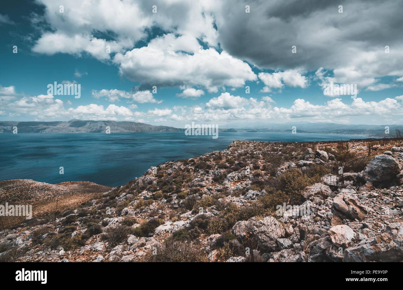 Panoramablick auf Felsen und Strand mit Himmel und Wolken auf Kreta, Griechenland. Eine herrliche Landschaft mit kristallklarem Wasser und die Felsen gegen einen tiefen Stockbild