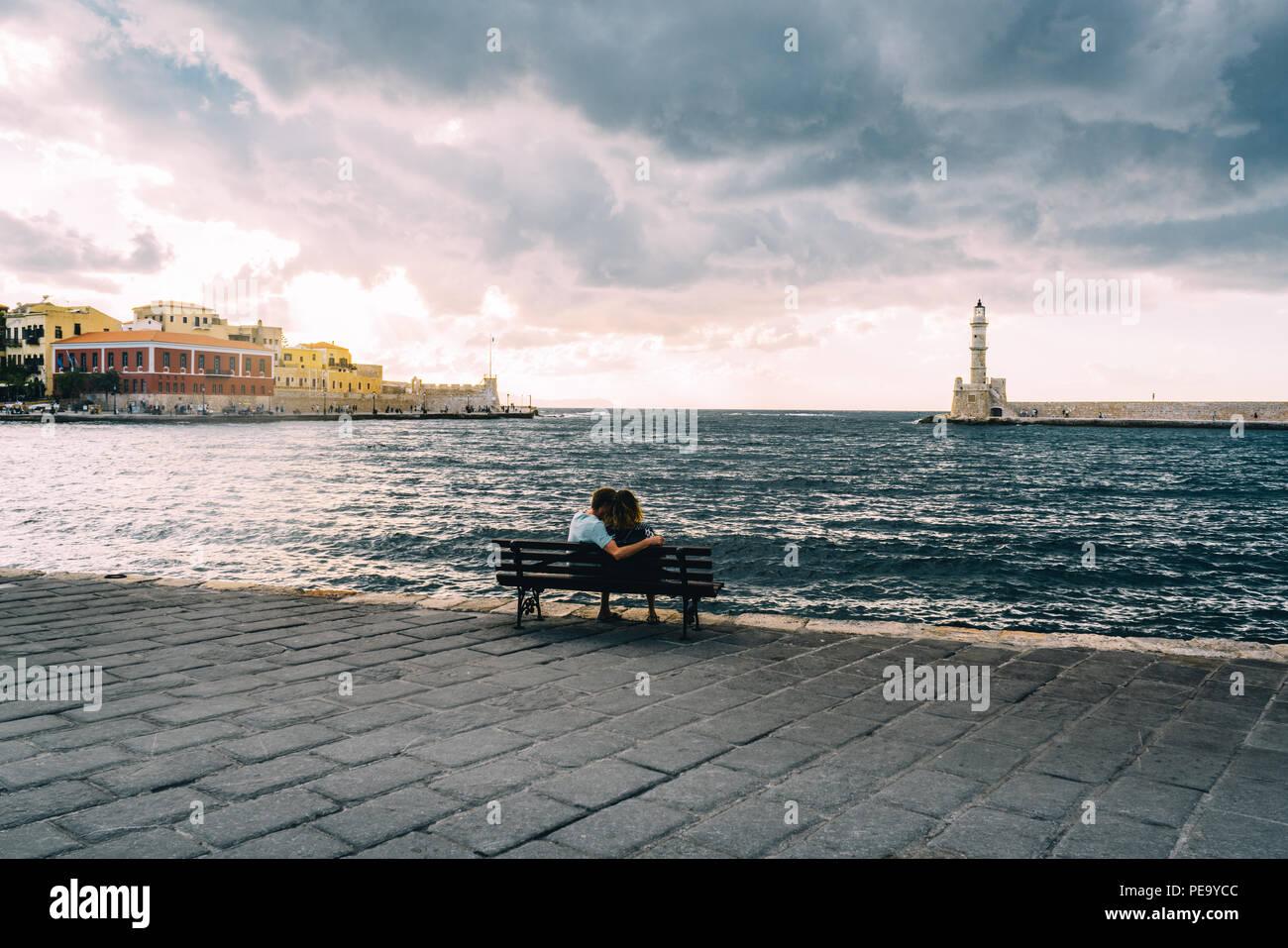 Chania, Kreta, Griechenland - August 2018: Paar sitzt auf der Bank mit Panorama venezianischen Hafen am Wasser und Leuchtturm im alten Hafen von Chania bei Sonnen Stockbild
