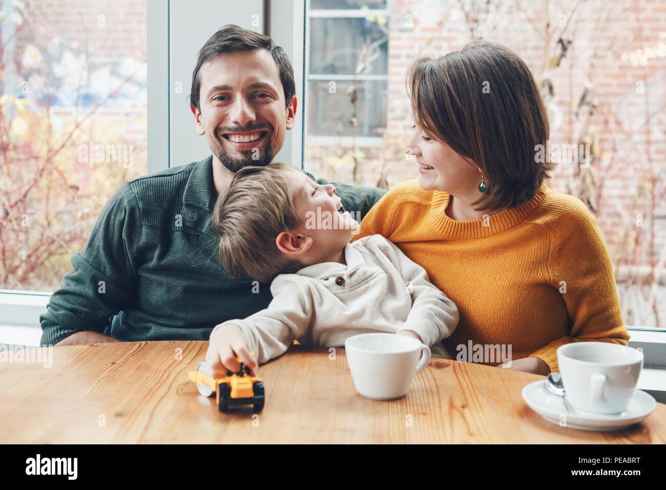 Portrait von weissen Kaukasischen glückliche Familie von drei Mutter, Vater und Sohn, im Restaurant Cafe sitzen am Tisch, lächelnd, authentischen Lebensstil Stockbild