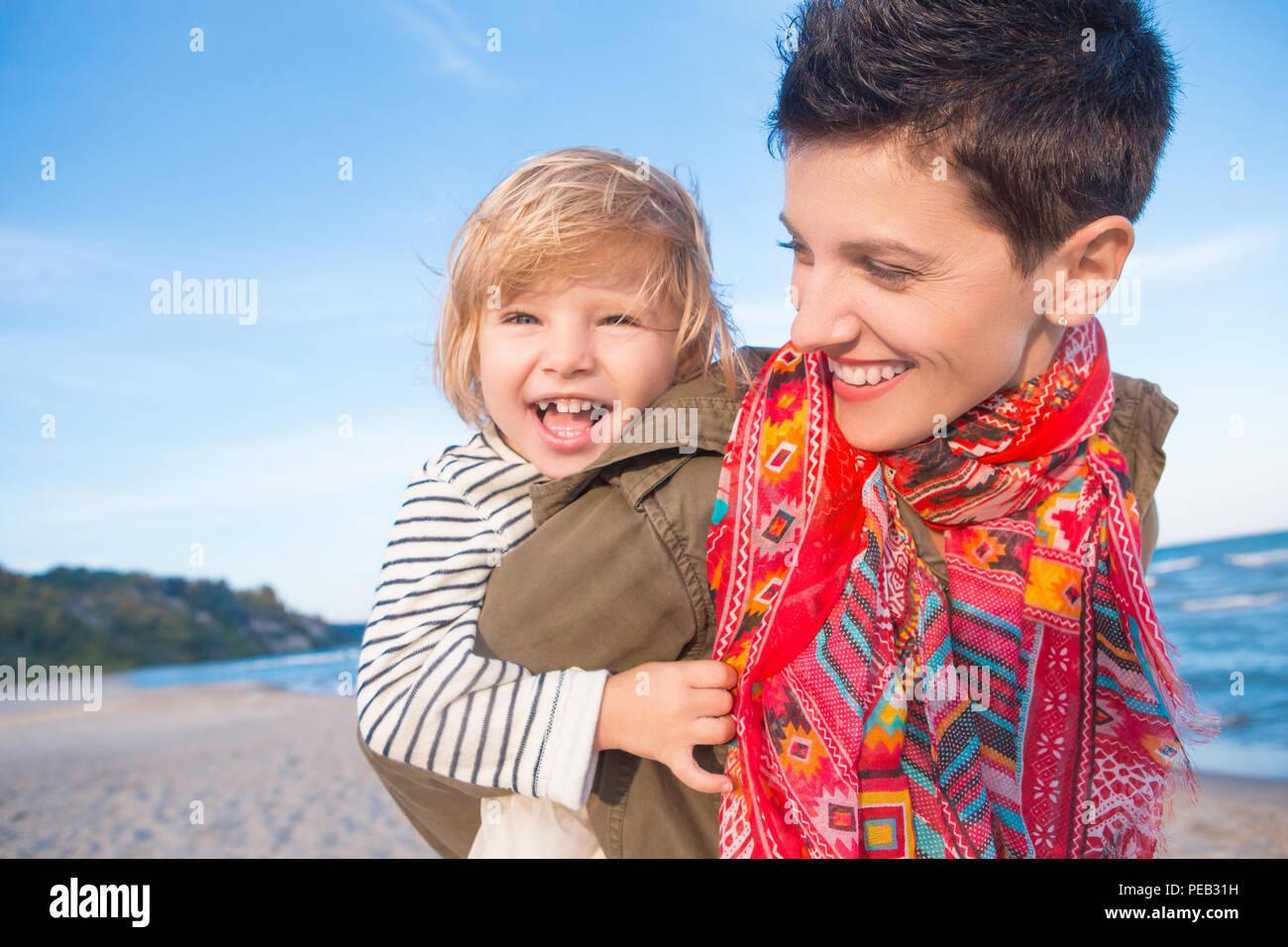 Group Portrait von lächelnden weißen weißen Mutter und Tochter baby girl, Huckepack, Reiten, Spielen, die auf Ozean Meer Strand bei Sonnenuntergang im Freien, Hap Stockbild