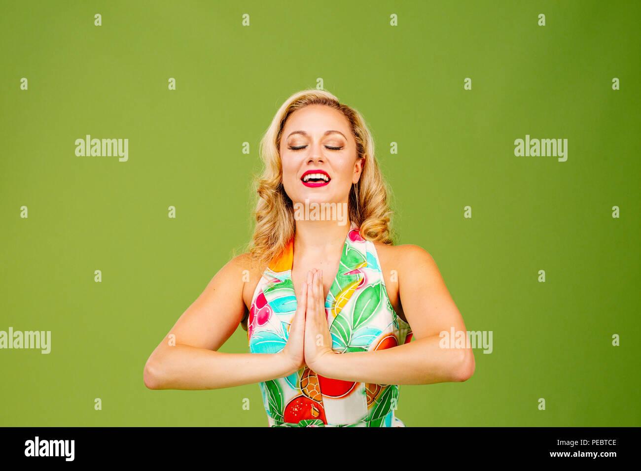 Schöne Frau mit Händen gemeinsam im Gebet und in der Mund offen, auf grüner studio Hintergrund isoliert Stockbild