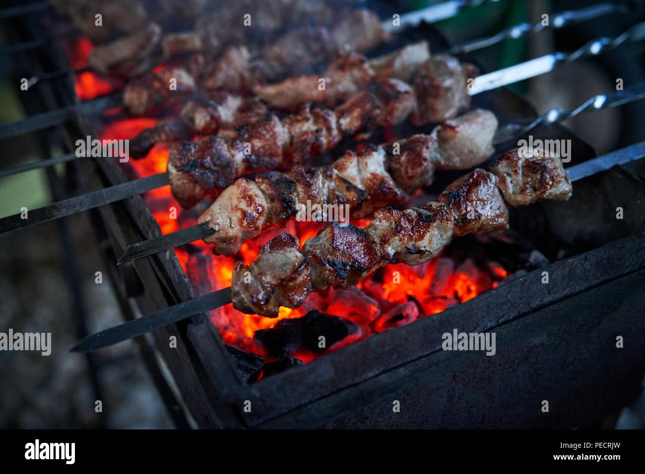 Schaschlik Vorbereitung auf einem Grill über Kohle. Stücke von Fleisch am Spieß. Shish Kebab auf Feuer, vorbereitet sein. Stockbild