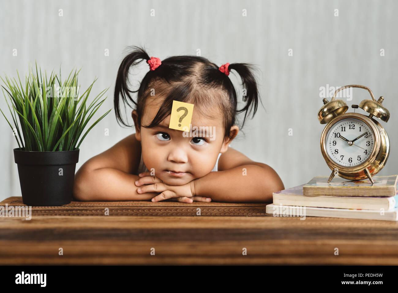 Süß und lookian verwirrt asiatischen Kleinkind mit Fragezeichen auf der Stirn. Konzept des Kindes lernen bildung, Wachstum und Entwicklung. Stockbild