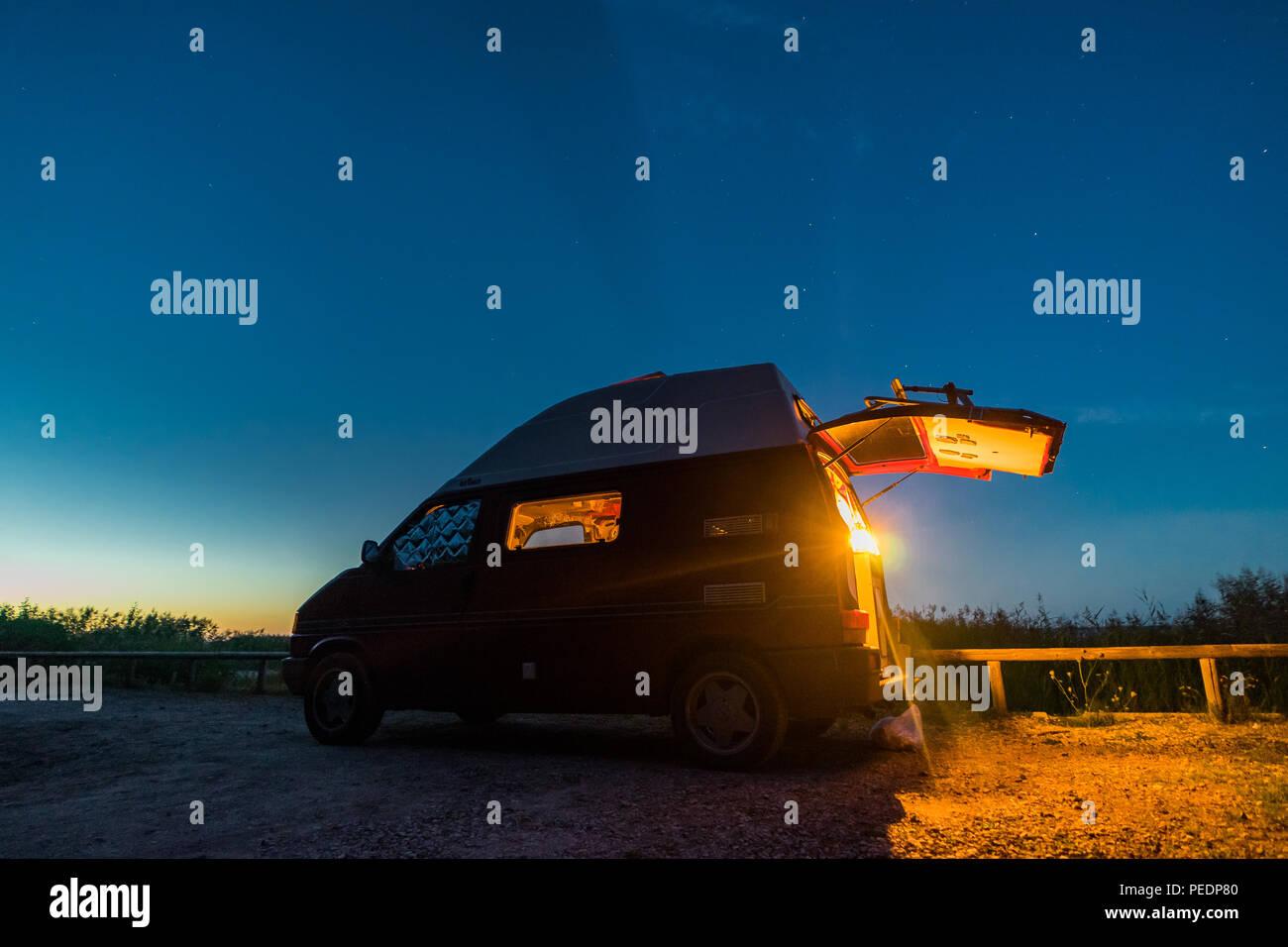 Litauen - August 2018: VW Transporter T4 in der Nacht auf einem Campingplatz in Litauen mit Licht im Inneren. Blick in Richtung Himmel und Sterne im backgrou Stockbild