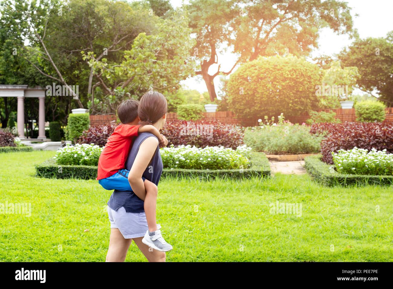 Mutter und Sohn Huckepack im Park im Sommer. Stockbild