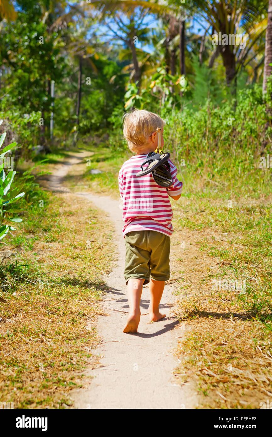 Gerne barfuß Kind allein am Strand von Pfad, der Dschungel kleiner Junge erkunden Schuhe tragen auf Stick. Familie Reisen, Lifestyle, Outdoor wandern aktivität Stockbild