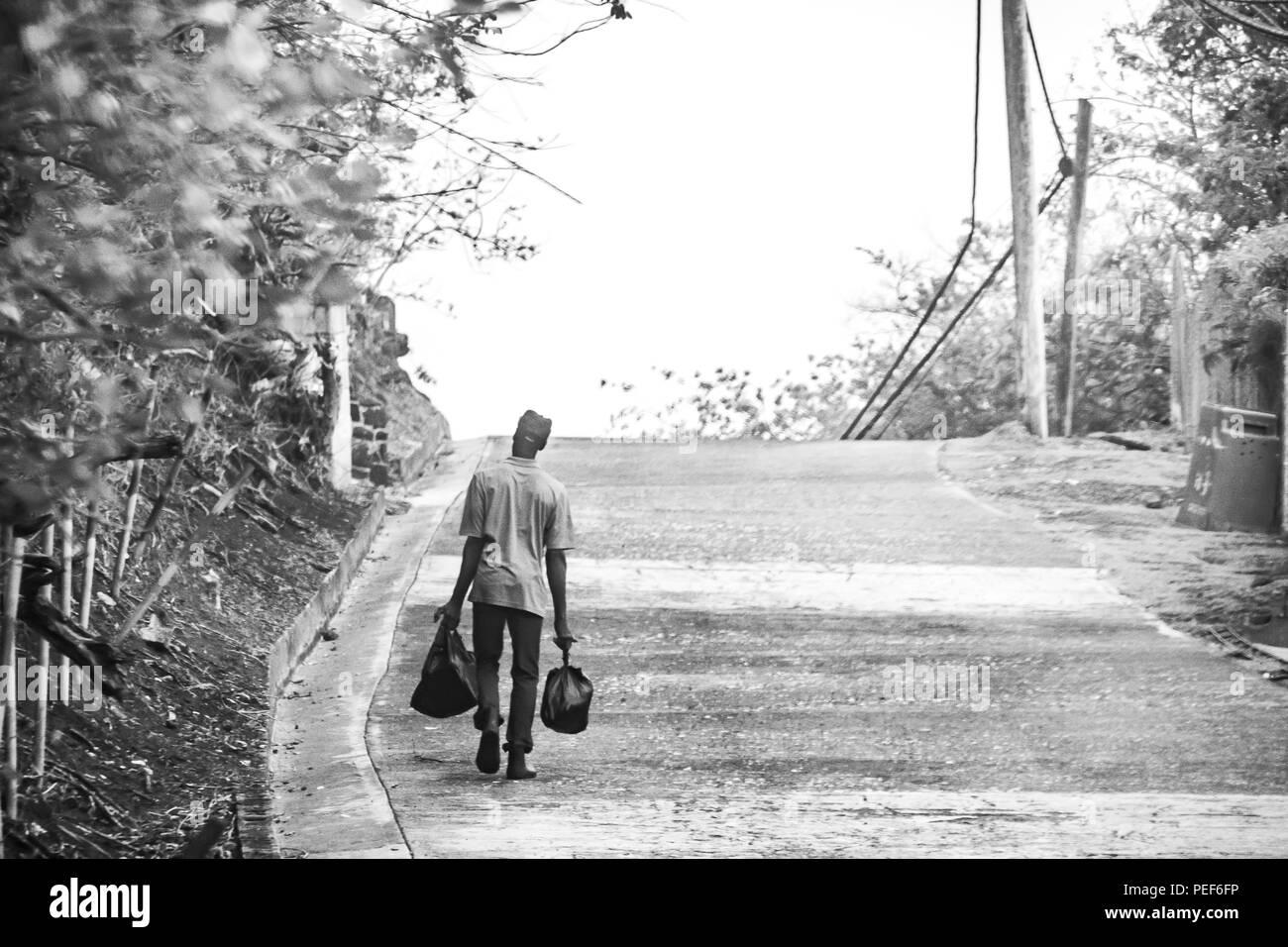 Mann zu Fuß die Straße runter auf der Insel Carriacou, Grenada Stockbild