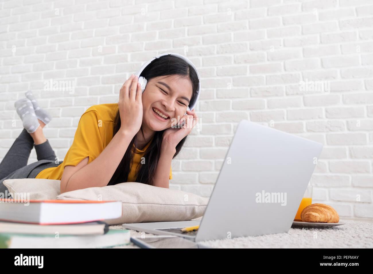 Asiatische Frau Musik hören und Laptop zu Hause zu arbeiten. Die Frau legte sich auf Teppich an der Wand. online arbeiten Lifestyle Stockbild