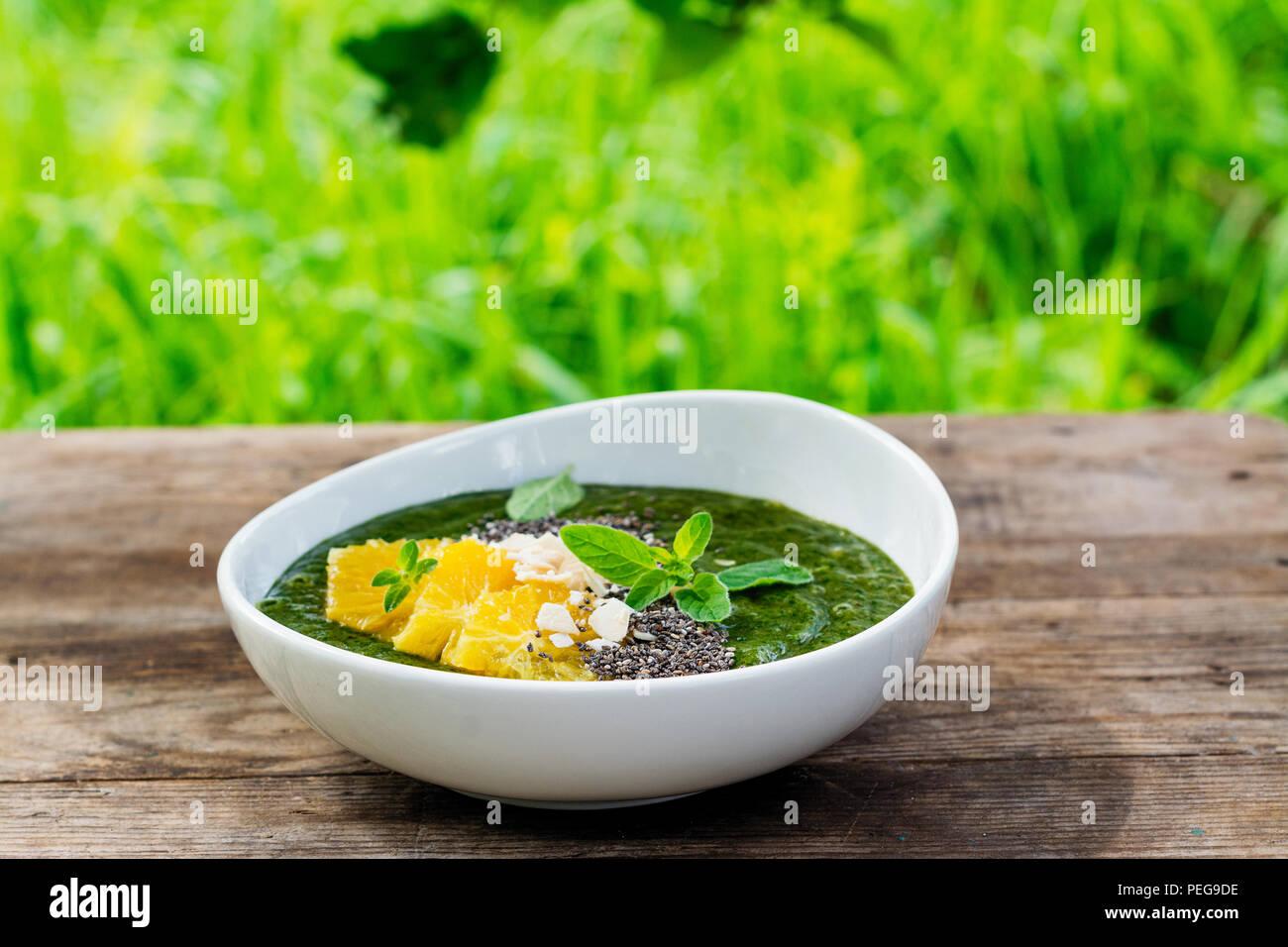 Grüne smoothie Schüssel mit Banane, Spinat, Chia Samen und Orangen Stockbild