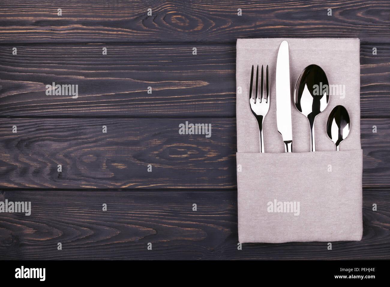 Satz von Gabel, Löffel, Teelöffel und Messer mit Bettwäsche Serviette auf Holztisch. Ansicht von oben. Stockbild