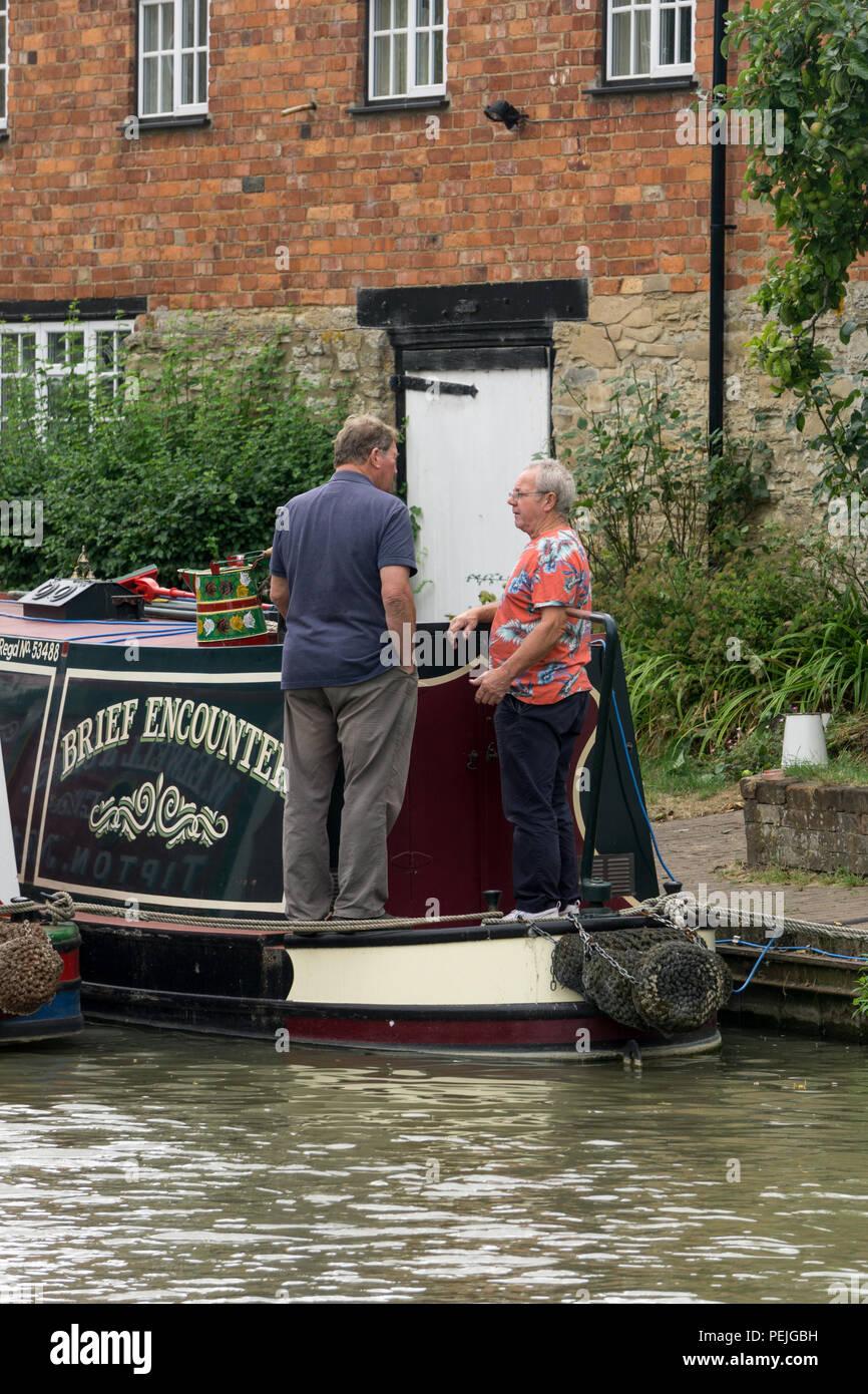 Zwei Männer mittleren Alters in einem Chat auf einem Narrowboat namens kurze Begegnung; Grand Union Canal, Stoke Bruerne, Northamptonshire, Großbritannien Stockbild