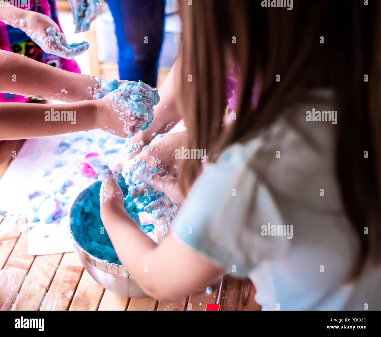 Eine Gruppe junger Mädchen, Kinder machen ein Durcheinander mit cremiger Schleim an einem Geburtstag Stockbild