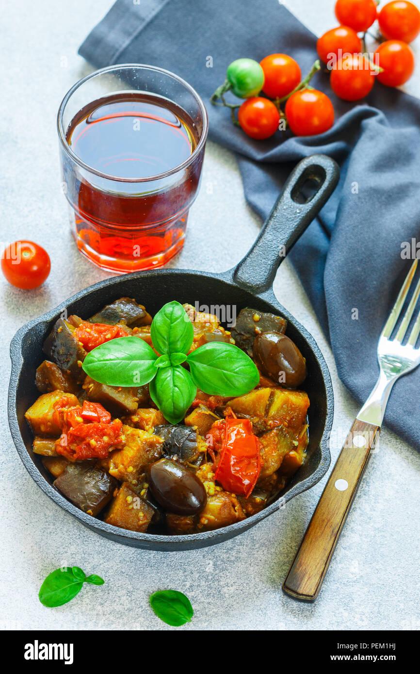 Caponata ist ein traditionelles sizilianisches Gericht. Eintopf mit Gemüse - Auberginen, Tomaten, Zwiebeln, Basilikum und Oliven mit Gewürzen und Gewürzen. Selektiver Fokus Stockbild