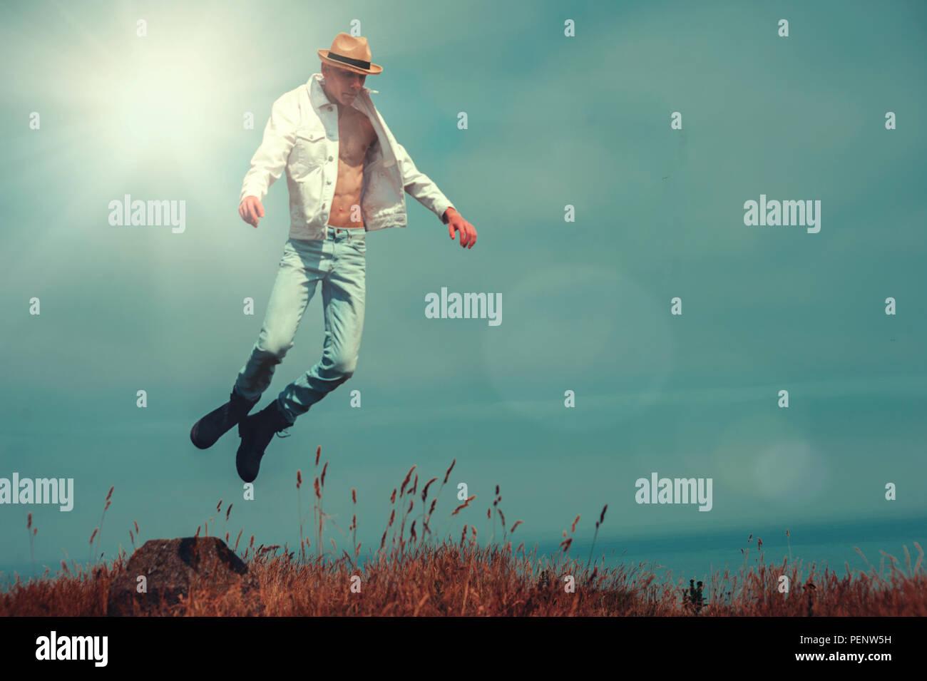 Junger Mann fliegen in den Feldern auf dem Cliff Stockfoto