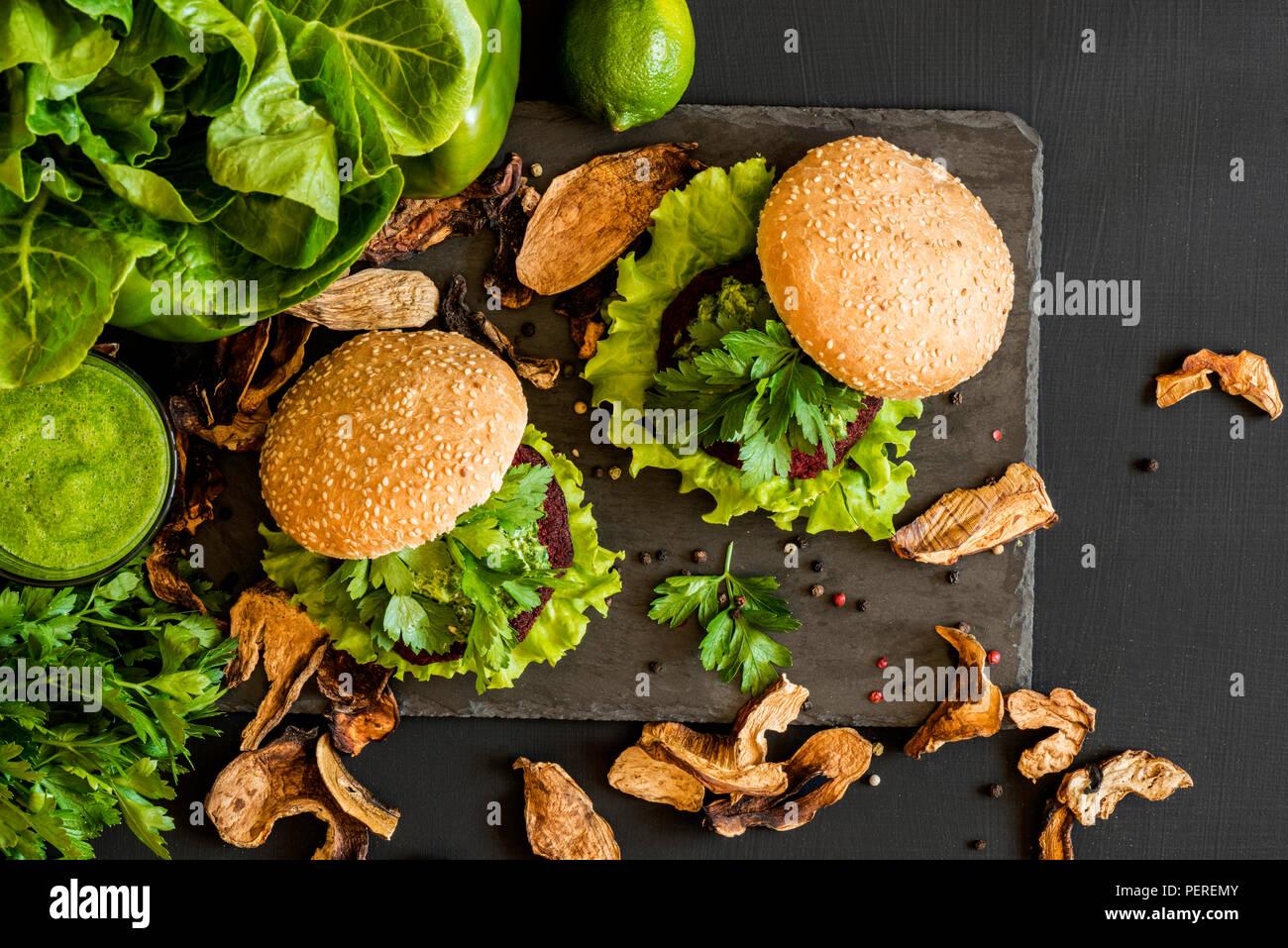 Vegane Burger mit Zuckerrüben Schnitzel und grüne Smoothies auf schwarzem Hintergrund. Gesund Vegan essen. Detox Diät. Stockfoto