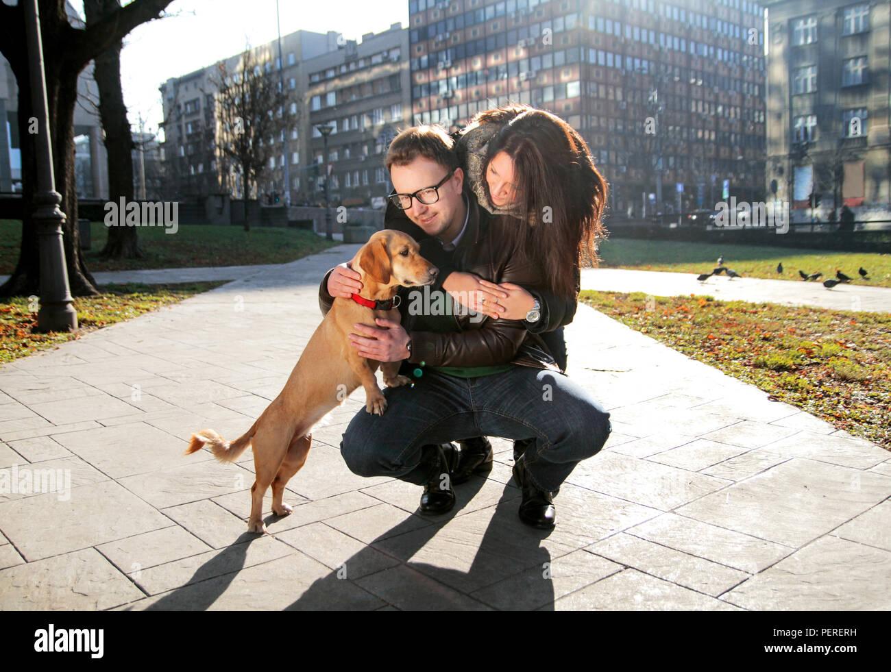 Freundin umarmen junger Mann, während er geduckt und der Hund kuscheln und alle genießen Sie einen schönen Tag im Park. Junges Paar mit Hund genießen. Stockbild