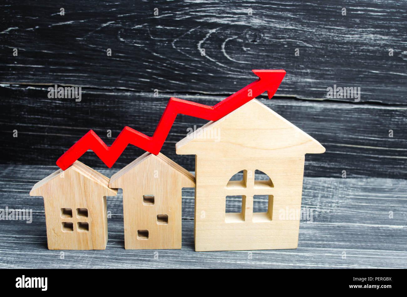 Holzhäuser in einer Reihe von klein bis groß mit einem roten Pfeil nach oben. Konzept der hohe Nachfrage nach Immobilien. zur Steigerung der Energieeffizienz der Wohnungen. r Stockbild