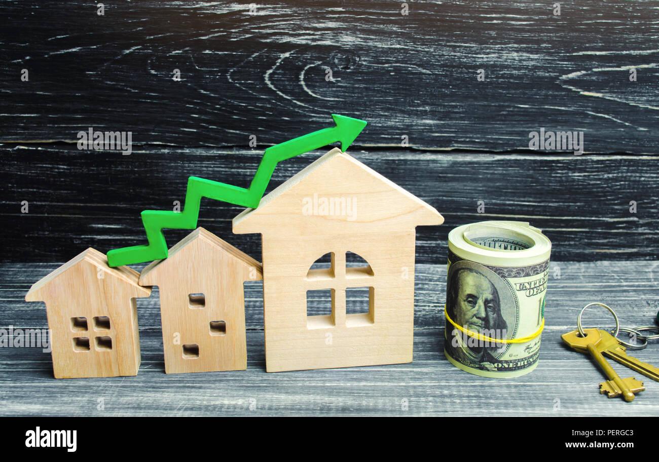 Holz- Häuser stehen in einer Reihe von klein bis groß mit einem grünen Pfeil nach oben. Konzept der hohe Nachfrage nach Immobilien. zur Steigerung der Energieeffizienz der Wohnungen. Stockbild