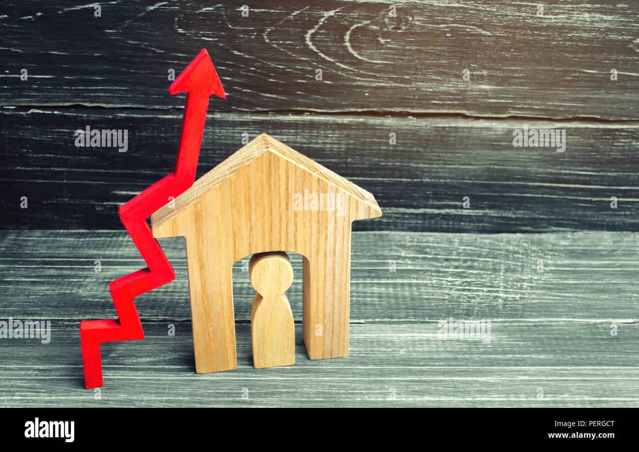 Holzhaus mit einem Mann nach innen. roter Pfeil nach oben. Konzept der hohe Nachfrage nach Immobilien. zur Steigerung der Energieeffizienz der Wohnungen. Anstieg der Immobilienpreise. Stockbild