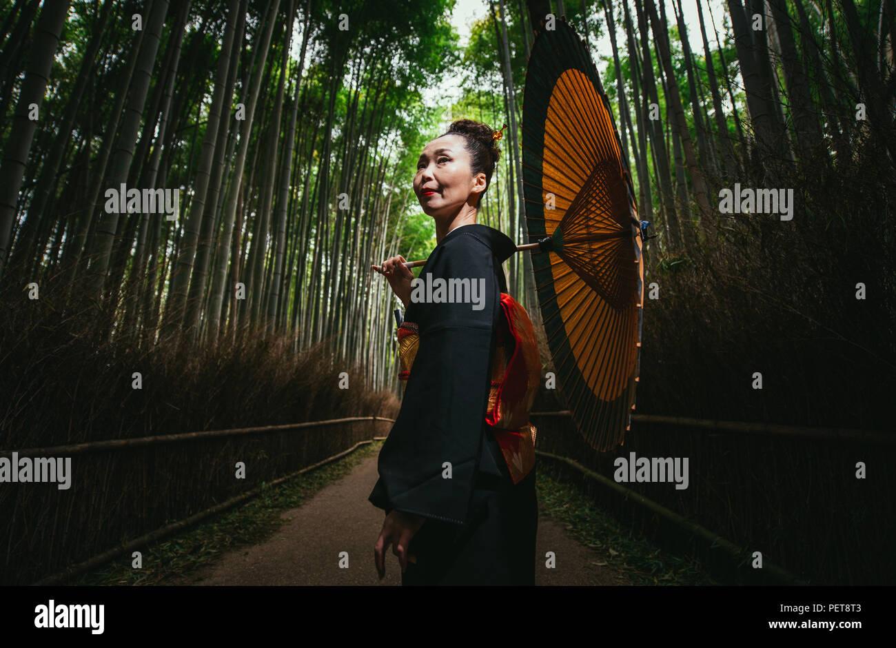 Schönen japanischen ältere Frau zu Fuß im Bambuswald Stockbild