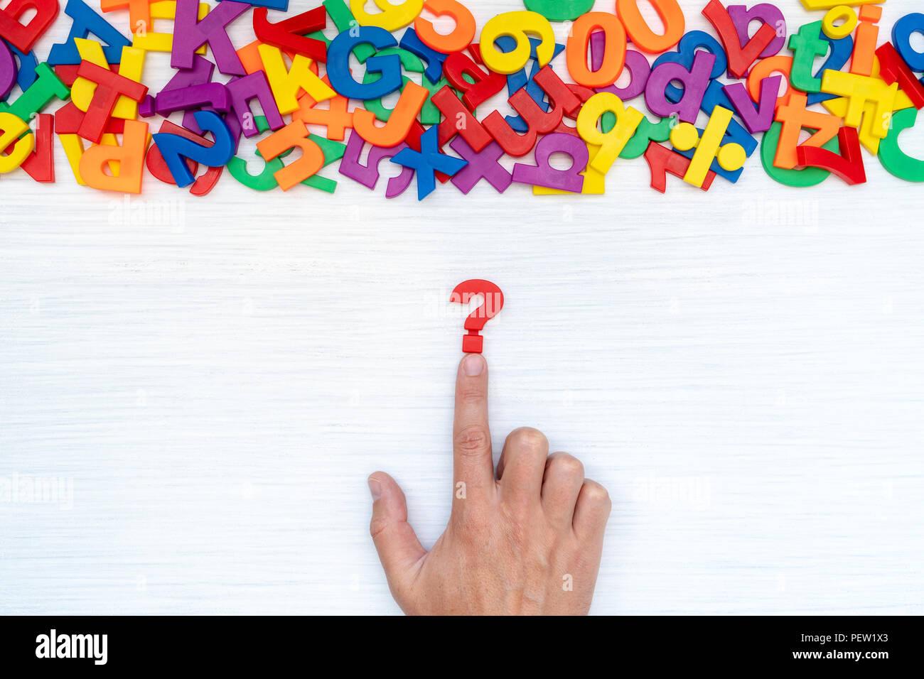 Hand mit Fragezeichen auf dem Tisch mit vielen Kunststoff Zahlen und Buchstaben. Konzept für Verwirrung oder Neugier. Stockbild