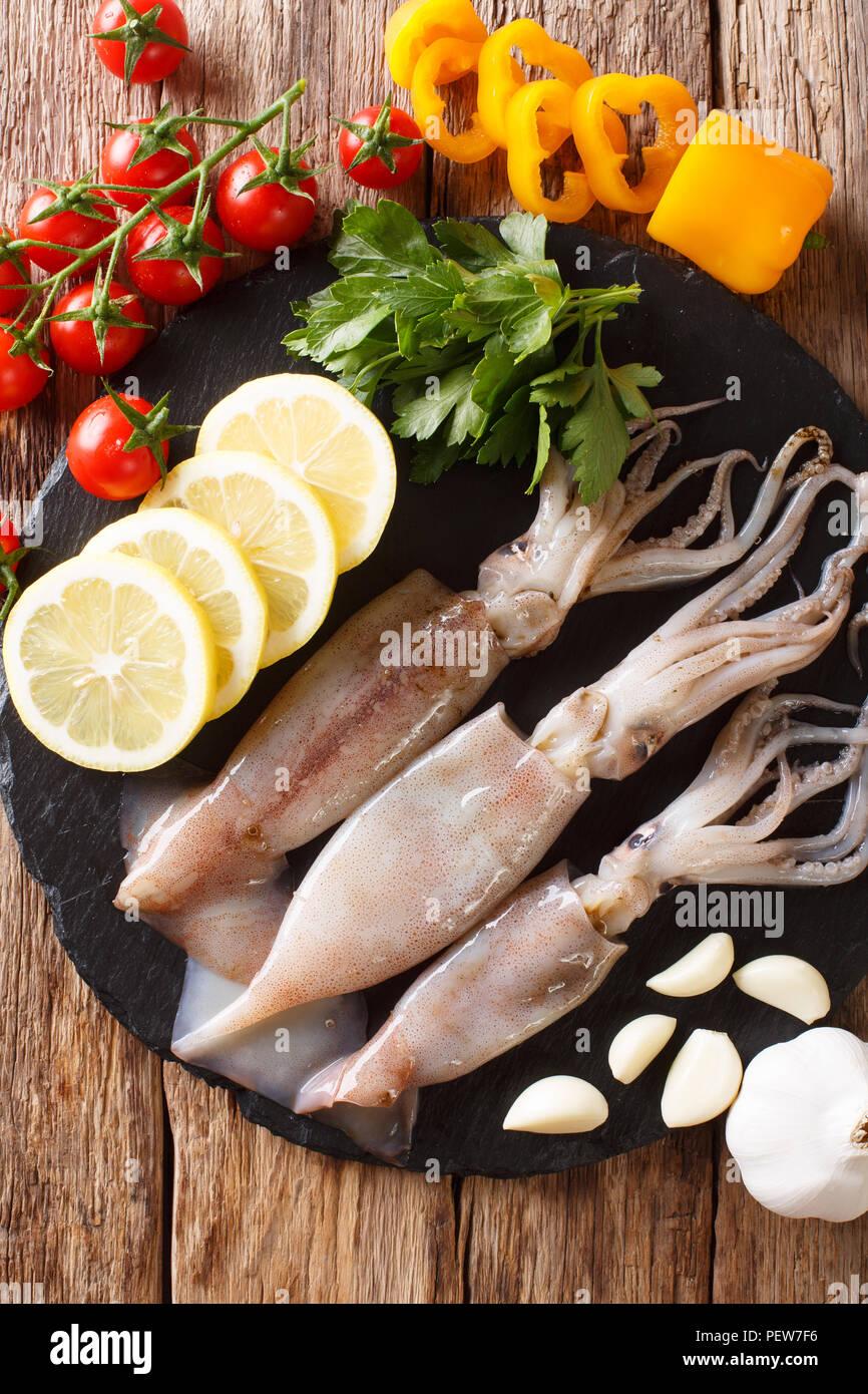 Meeresfrüchte frische Tintenfische mit Tentakeln close-up und Gemüse für die Küche auf den Tisch. Vertikal oben Ansicht von oben Stockbild
