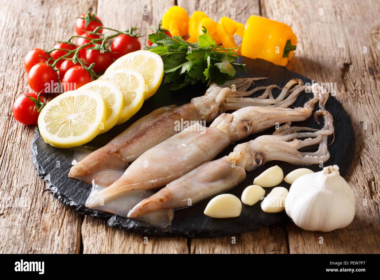 Rohe Meerestiere zum Kochen squid Close-up und Zutaten auf einer Schiefertafel Board auf einem Tisch. Horizontale Stockbild