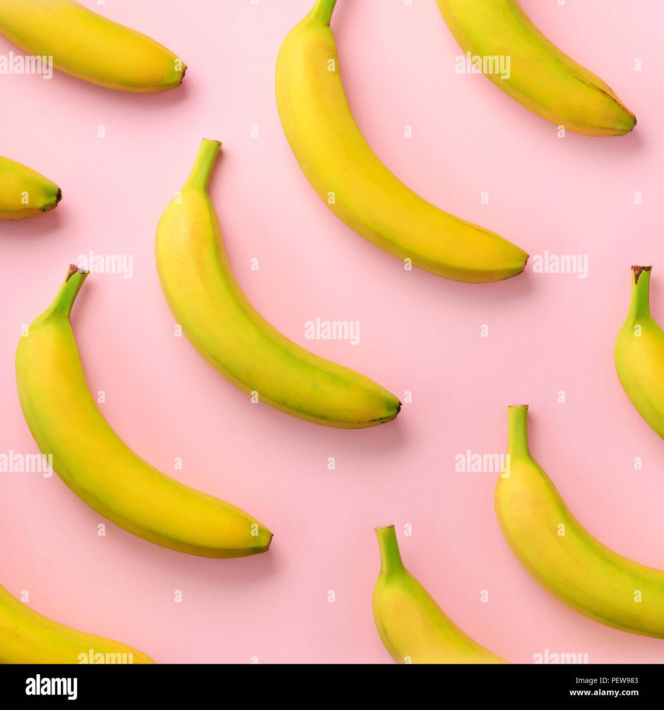 Bunte Obst Muster. Bananen über rosa Hintergrund. Platz crop. Ansicht von oben. Pop Art Design, kreative Sommer Konzept. Minimale flach Stil Stockbild