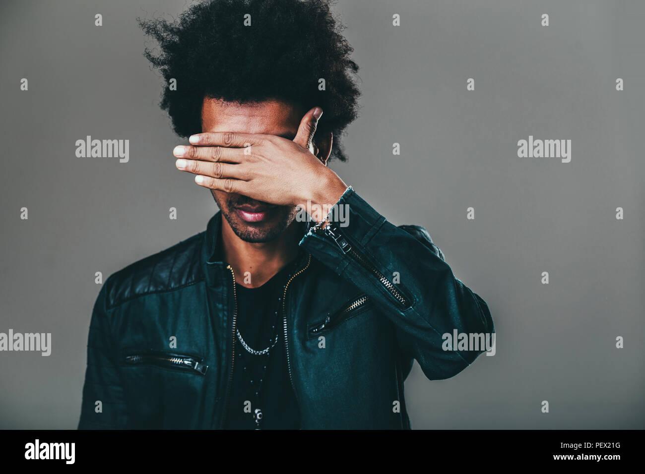 Nicht erkennbare unrasiert afrikanische amerikanische Mann mit zerzausten Haare macht facepalm Geste, die Augen während schäme, stehend gegen leere St Stockbild
