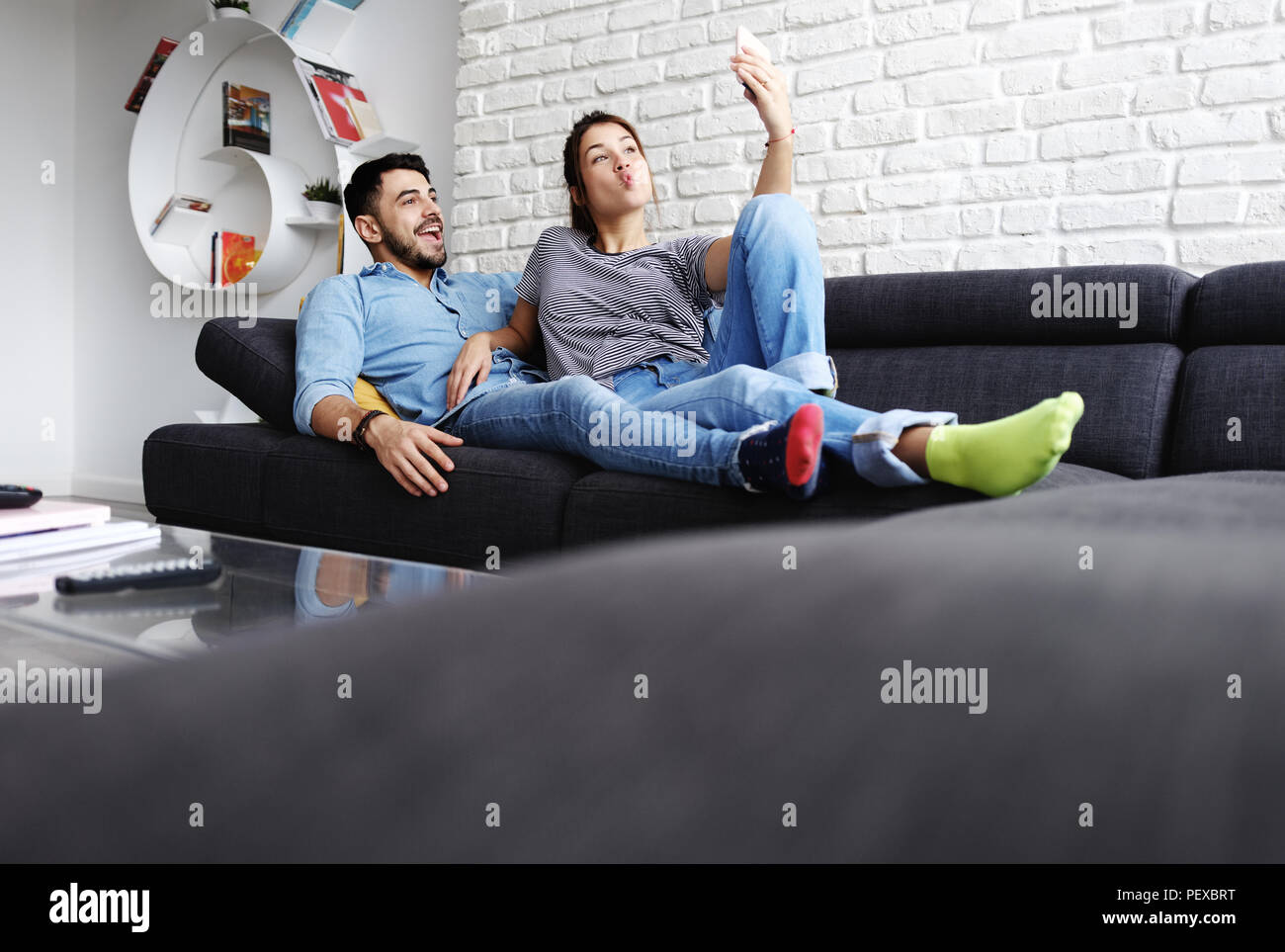 Junges Paar unter Selfie auf dem Sofa zu Hause Stockbild