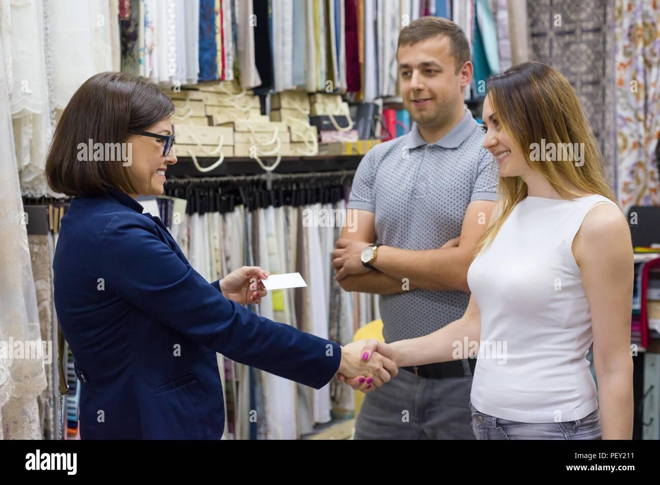 Weibliche store Eigentümer gibt Visitenkarte auf ein junges Paar. Small Business home Textil shop Stockbild