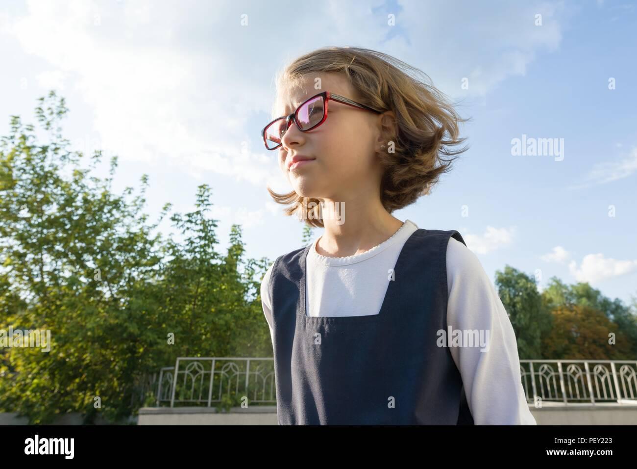 Outdoor Portrait eines kleinen Schüler, Mädchen mit Brille, einheitlich. Schule, Bildung, Wissen und Kinder, kopieren Raum Stockbild
