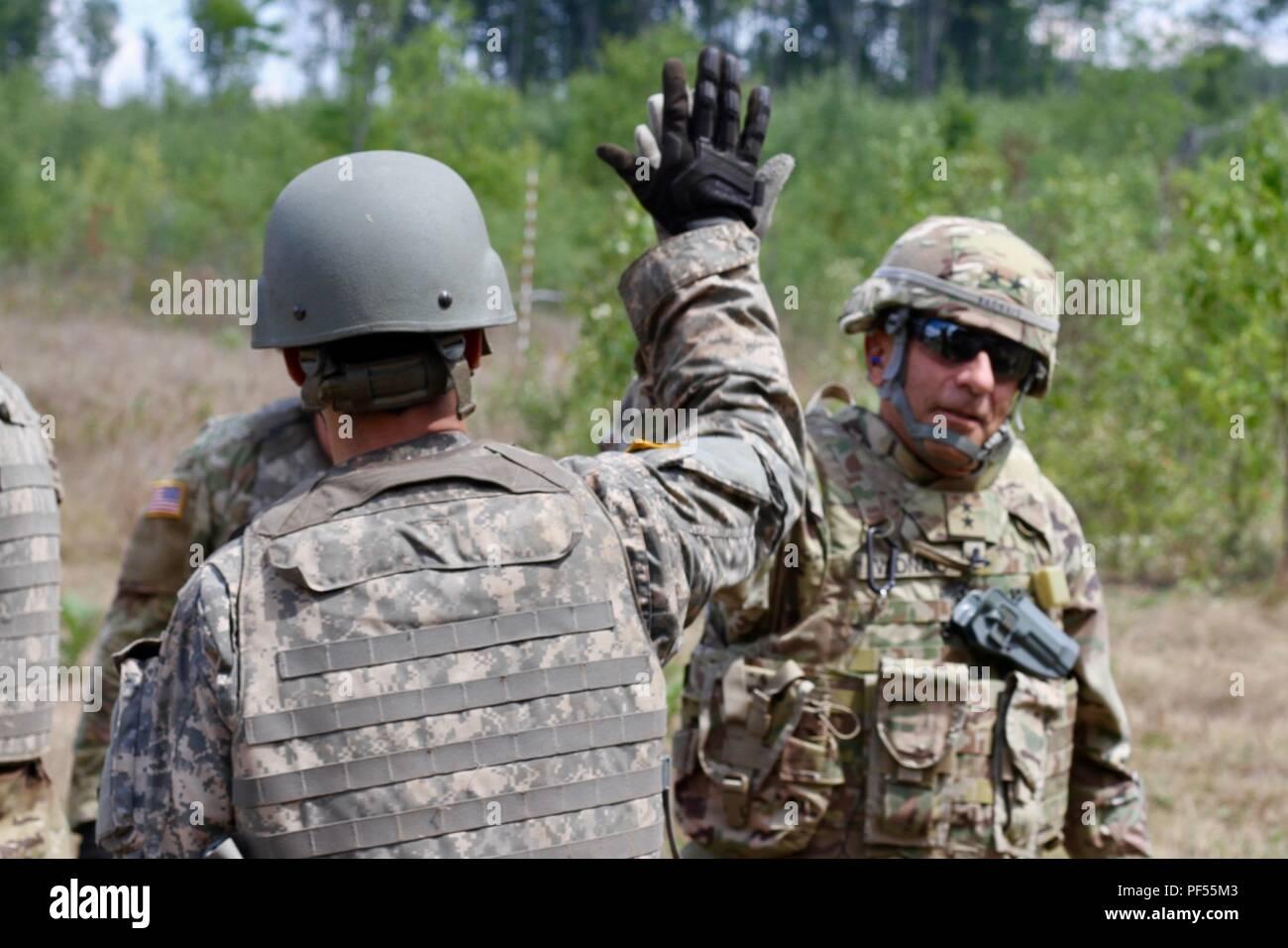 CAMP ÄSCHE, Mich - Generalmajor Gregory J. Vadnais, der Adjutant General und Leiter des Militärischen und Veterans Affairs für die Michigan National Guard, high-fives ein Soldat von der Batterie EIN, 1.BATAILLON, 103 Field Artillery Regiment, Rhode-Island Army National Guard, nach dem Brennen die M777 Haubitze, Aug 9, 2018 in Camp Äsche, mich Vadnais besucht Rhode Island National Guard Soldaten aus der 103 FA Teilnahme an Northern Strike eine gemeinsame, multinationalen, kombinierte Waffen live fire Übung im Camp Äsche, Michigan (USA Army National Guard Foto von 1 Sgt. Sara Robinson) Stockbild