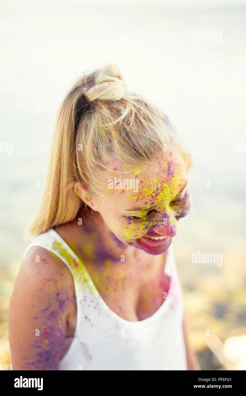 Das Festival von Holi. Die Freude und Glück. Farbe im Gesicht. Blonde Mädchen. Das Festival von Holi. Die Freude und das Glück. Farbe im Gesicht. Mädchen der Blondine. Das Lächeln auf ihrem Gesicht, Glück Stockbild