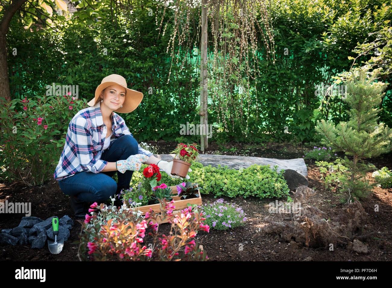 Schöne weibliche Gärtner an Kamera suchen, mit Blumen in Ihrem Garten gepflanzt werden. Gartenarbeit Konzept. Stockbild