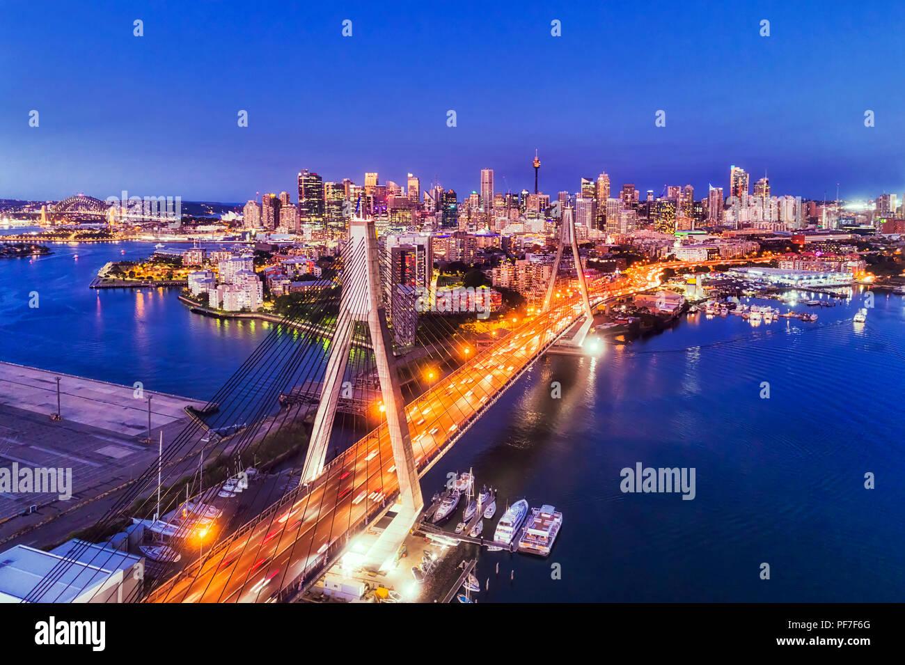 Helles Kabel Anzac Brücke über den Hafen von Sydney, die zu Stadt CBD bei Sonnenuntergang unter dark blue sky in Australien beleuchtet. Stockbild