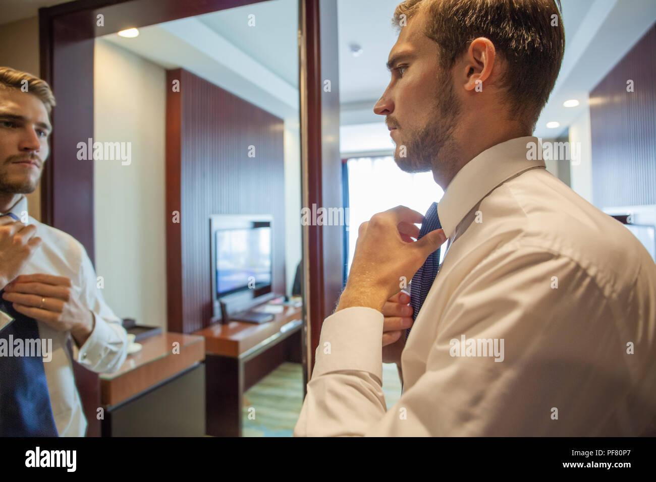 Personen, Business, Mode und Kleidung Konzept - Nahaufnahme der Mann im Hemd Dressing up und Einstellung der Riegel am Hals zu Hause. Stockbild