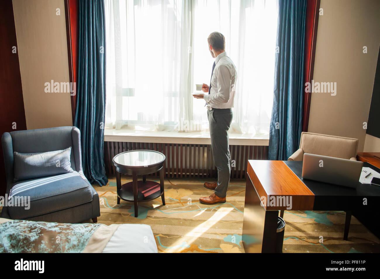 Geschäftsreise und Personen Konzept - Geschäftsmann trinken Kaffee im Hotel Zimmer. Stockbild