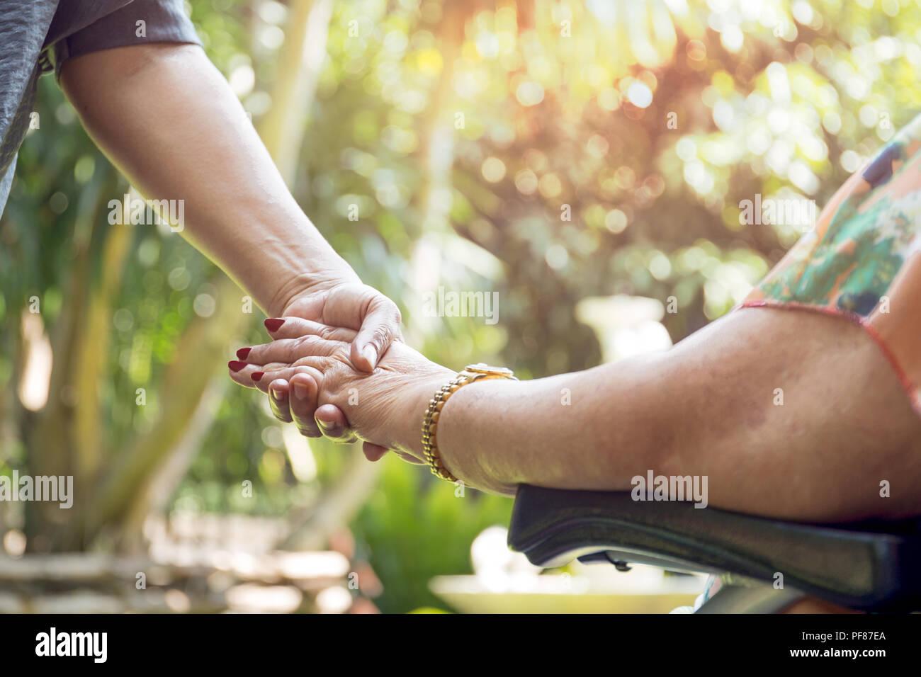 Ältere Frau im Rollstuhl Hände mit junge Frau draußen im Sonnenlicht Stockbild