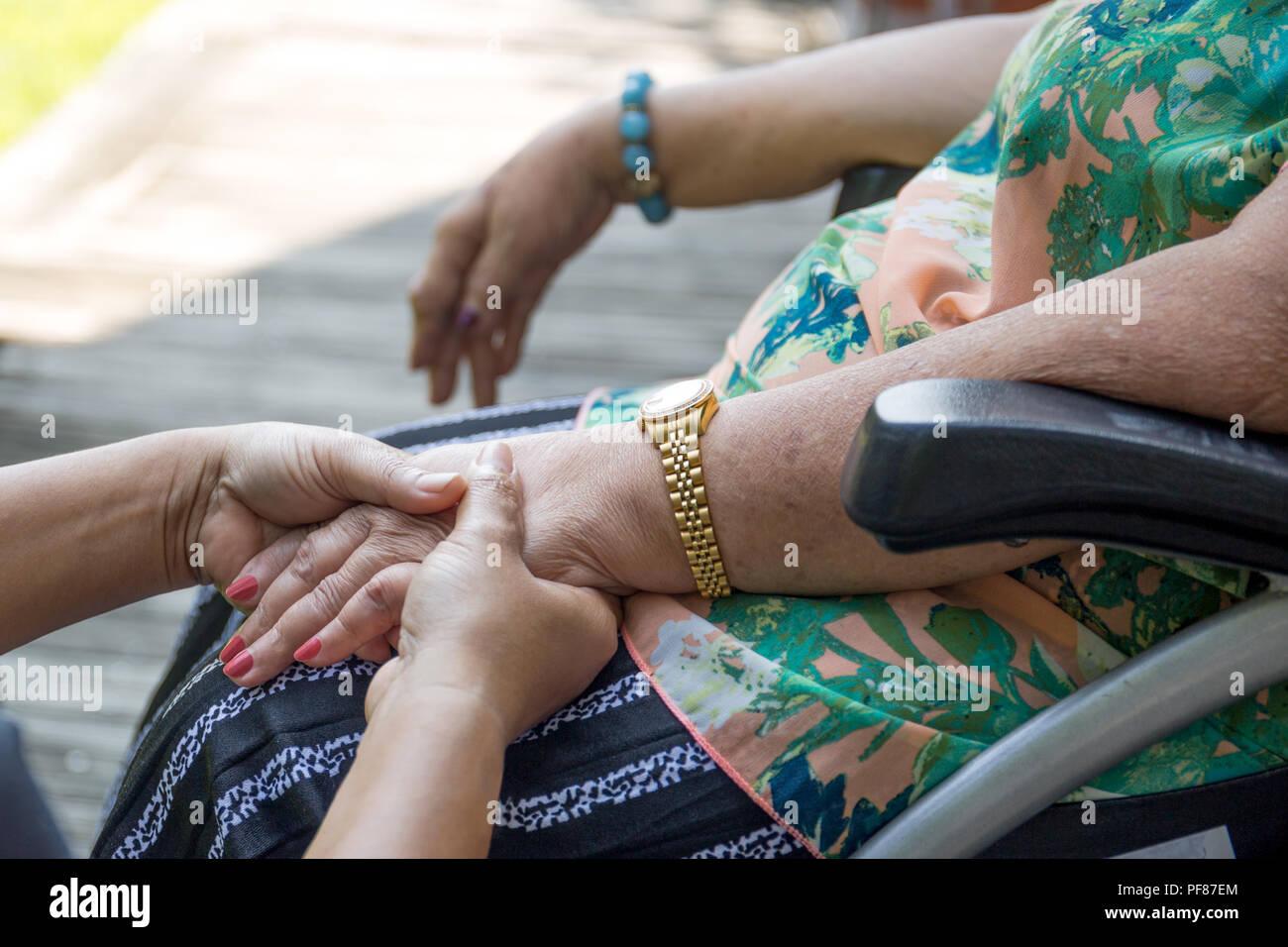 Ältere Frau im Rollstuhl Hände mit Betreuer in den Garten Stockbild