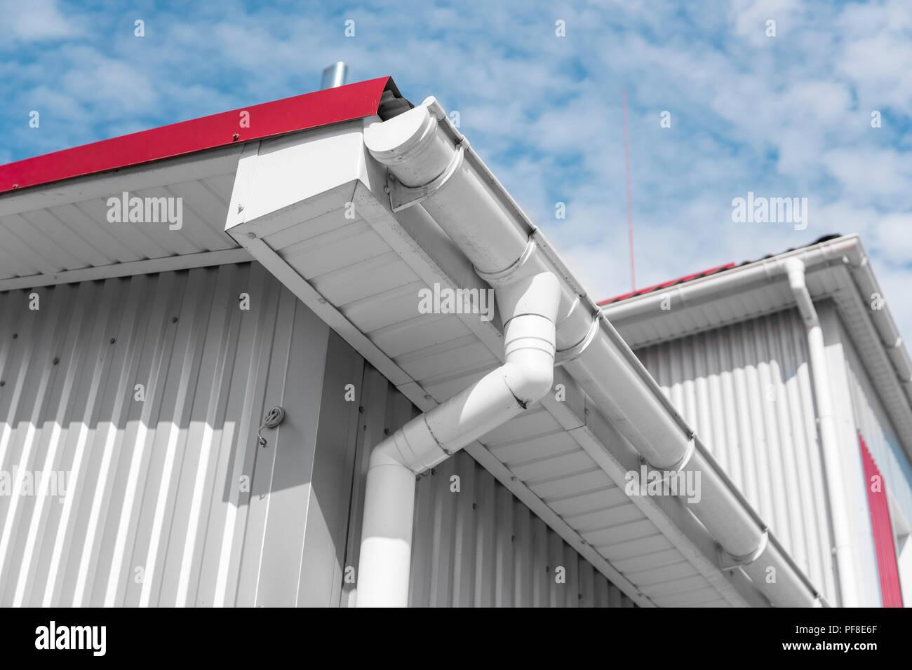 weiß regenrinne auf einem haus mit rotem dach gegen den blauen