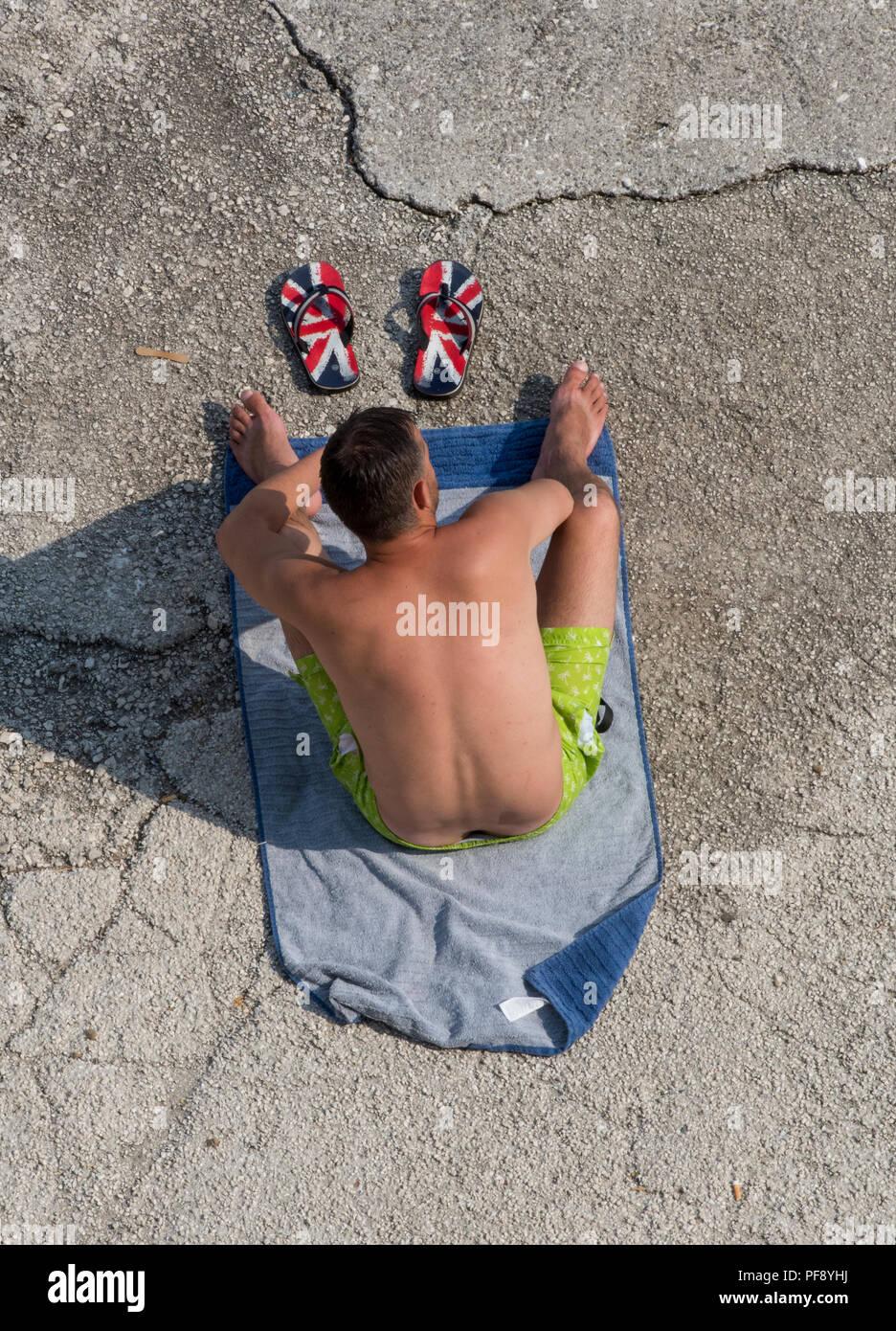 a574451879e1a Mann sitzt auf einem Handtuch am Strand Sonnenbaden mit Union Jack Flagge  britischen flip-flops vor ihm. Patriotische an Feiertagen.