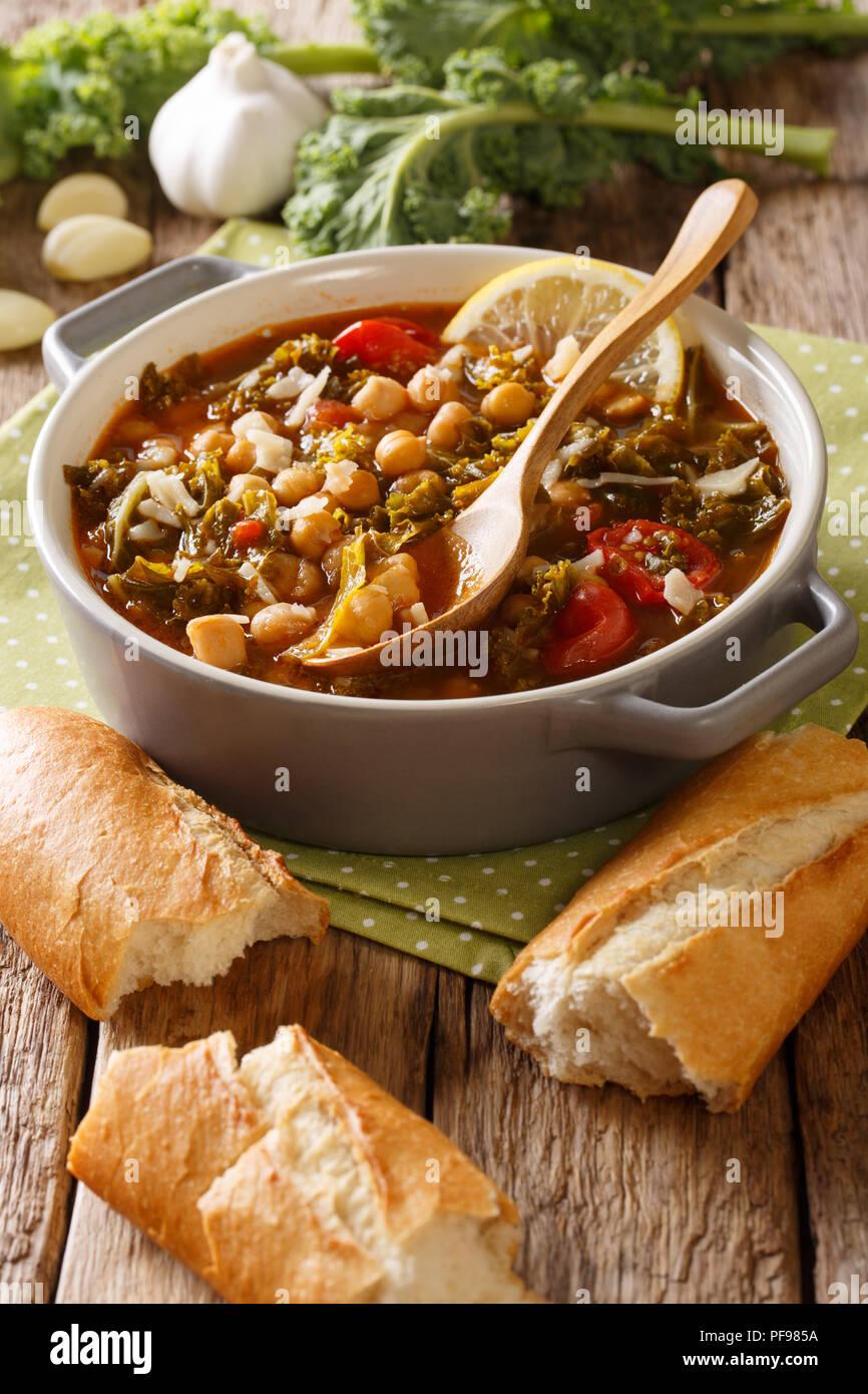 Eintopf aus Kichererbsen, Grünkohl, Tomaten, Knoblauch und Kartoffeln mit Parmesan close-up in einer Schüssel auf dem Tisch. Vertikale Stockbild